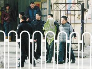 张某头上罩着被单,被警方带走。