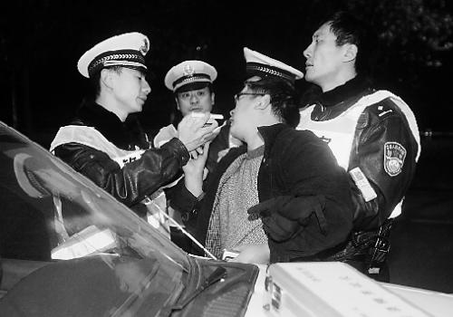 交警将酒精测试仪送到嘴边,桑塔纳司机左躲右闪。
