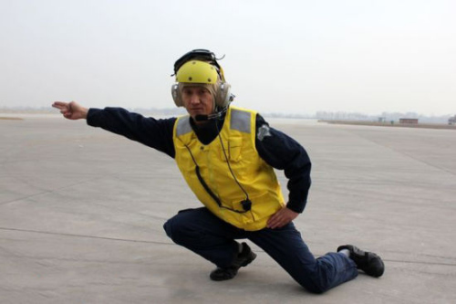 特别是飞机起飞时,甲板机务工作者的起飞动作指令,左腿屈膝下蹲,右臂
