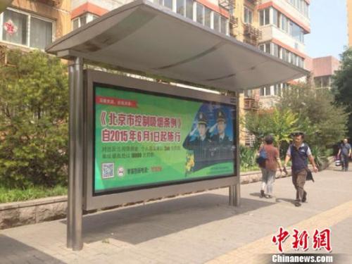 """6月1日起,被称为""""史上最严控烟令""""的《北京市掌握抽烟章程》正式实施。图为北京陌头公交车站左近告白屏的提醒。 中新网记者 马学玲 摄"""
