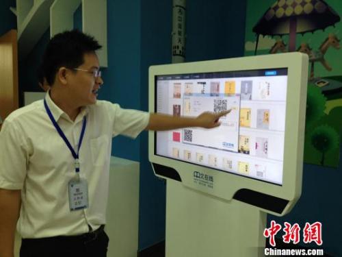 图为潍坊市图书馆里工作人员正在为大家演示如何用触屏机阅读儒学典籍。曾洁 摄