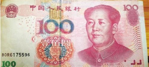 """资料图:这张百元币,其他的一切正常,只是在正中间""""100""""字样的上方,又多了一个""""100""""的水印。图片来源:钱江晚报"""