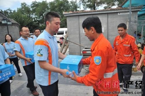 工作人员向西城环卫环丽中心三班李新田赠送饮用水