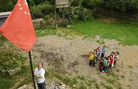 资料图:一位乡村教师正在升国旗。