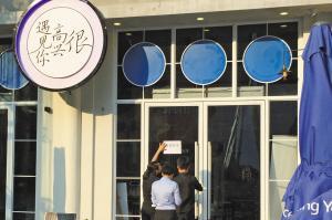 """""""很快乐碰见你""""餐馆作业人员在粘贴""""停息停业""""的告诉。图像来历:国家宁波网"""