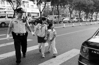 图为中关村三小万柳校区门前,民警护送孩子们过马路。林森摄