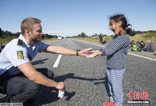 在凌乱的灾黎潮中,克日走红收集的丹麦差人与叙利亚灾黎小女孩游玩的相片,让人倍感和煦。