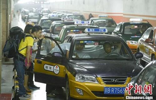 资料图:市民在北京西客站出租车候车点准备乘车。中新社发 侯宇 摄