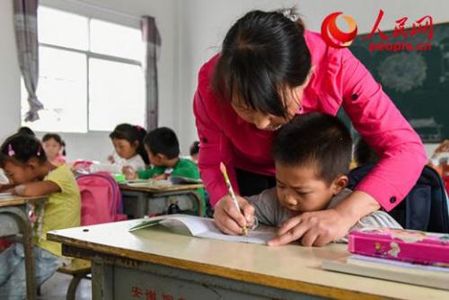 吴玉华是天台联合小学的一名普通女教师,她负责一年级和学前班孩子的几乎所有课程。每天,她都要从县城家中乘约2小时的车来到这里教书。人民网 苗子健摄