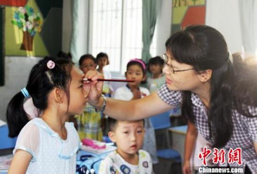 图为,武汉梨园小学一年级老师正在给学生点朱砂。 徐金波 摄