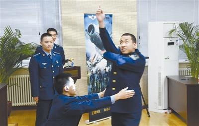 """""""金头盔""""获得者陈鸿程指导飞行学员杨子霄模拟飞行。"""
