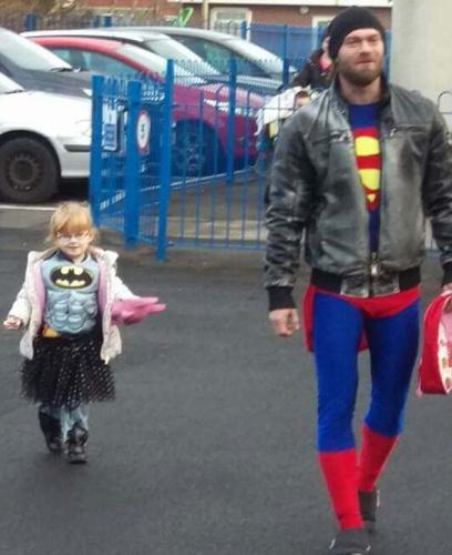 """英國老爸扮""""超人""""陪""""蝙蝠俠""""女兒上學被人拍下,照片隨即走紅網絡。(網頁截圖)"""