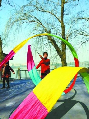 脱去冬装,挥起彩绸,今晨市民在北海公园晨练。