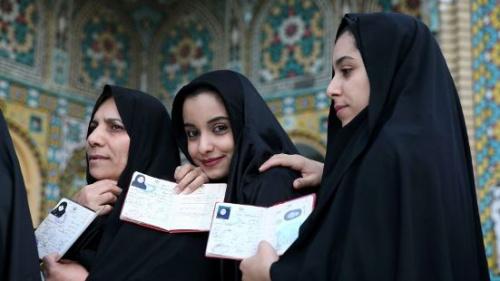 伊朗民众在投票前展示身份证件。(美联社)
