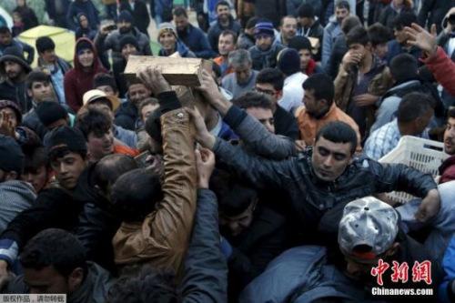 本地时刻2016年3月6日,希腊Idomeni,停留希腊与马其顿边界的移民簇拥争抢木料。