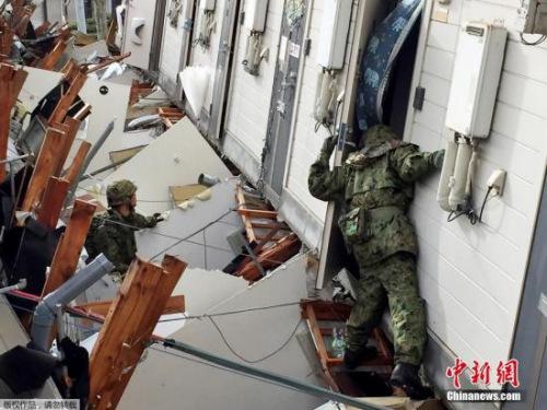 当地时间4月17日,日本熊本县震后见闻。救援人员在已经倒塌的公寓里挨家挨户进行搜救。