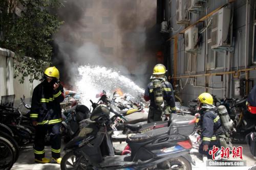 资料图:2015年6月5日上午,郑州一小区内电动车发生爆炸,现场浓烟滚滚。冯磊 摄