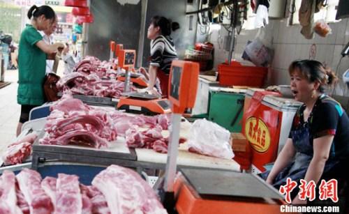 资料图。北京一菜市场的猪肉摊位门庭冷落。发 翟羽佳 摄