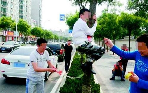 网传的新郎被用胶带绑在树上,屁股下燃放鞭炮。图片来源:齐鲁晚报