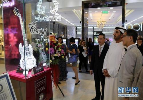"""5月22日,在阿联酋迪拜一个购物中心,阿联酋经济部副部长阿卜杜拉·萨利赫(右二)参观得到吉尼斯世界纪录认证的全球""""最昂贵吉他""""。"""