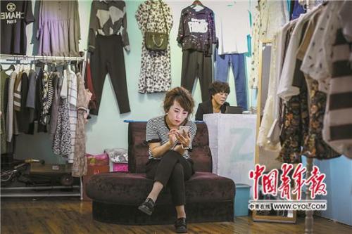 5月22日,一家位于康巴什繁华地段的购物中心,1990年出生的店主付姣玩手机打发时间。她17岁时从达拉特旗来到康巴什,现在每个月可以赚三四千元。