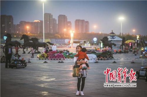 5月21日,康巴什区乌兰木伦湖广场,王俊霞抱着1岁多的女儿燕毅嘉在广场上散步。这里是康巴什入夜后人气最旺的地方。