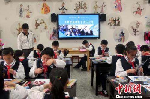 近40名小学生在木偶皮影艺术制作工作坊里学习皮影制作。邓霞 摄