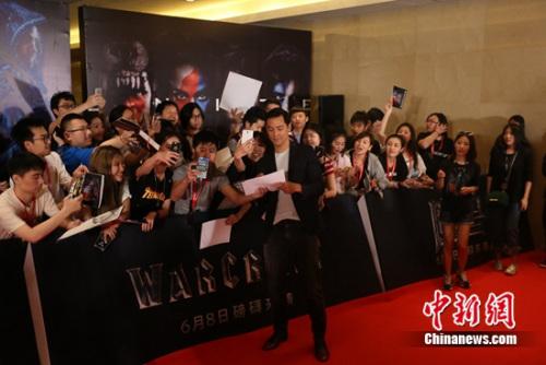 吴彦祖、在发布会红毯为现场粉丝签名