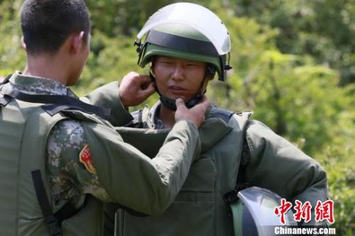 出征之前,扫雷官兵互相整理检查防护装具。 严浩 摄