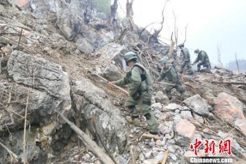 爆破后,官兵穿着厚厚的防护装具在陡峭的山崖雷场进行人工搜排。 郭赣荣 摄