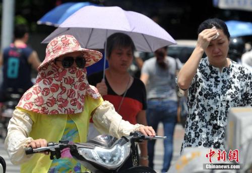 """6月1日,有着""""新四大火炉""""之称的福州发布高温橙色预警信号,各县市最高气温将升至35℃以上,内陆县市最高气温可达37-38℃。图为福州市民冒着高温出行。 张斌 摄"""