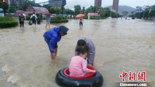 """图为武汉市江夏区遭遇暴雨袭击,该区城管部门工作人员利用轮胎、脚盆自制""""皮划艇""""转移被困群众。 钟欣 摄"""