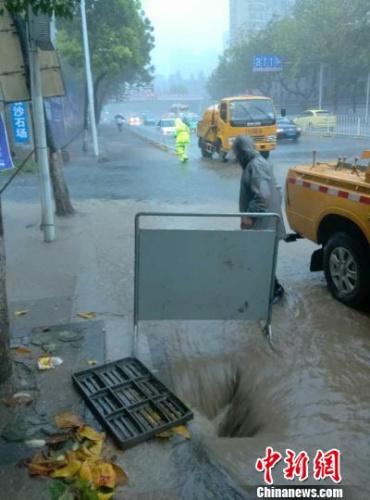 图为武汉市水务部门工作人员在鹦鹉大道朝阳路口段,揭开井盖排水。 陈怿 摄
