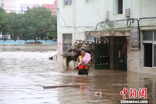 图为随州一名消防战士将被困水中的女童抱送至安全地带。 冯少勇 摄