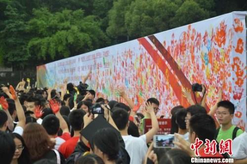 """资料图:2014年6月24日,湖南大学2014届本科生毕业典礼在湖南大学南校区体育场举行,数千名毕业生以鞠躬、拥抱以及""""涂鸦""""的方式来抒怀自己对母校的感恩。向一鹏 摄"""