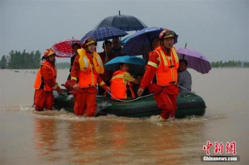 资料图:7月1日,湖北麻城遭遇特大暴雨袭击,导致该市境内多地山洪暴发、河水陡涨、民房进水、房屋倒塌、农田冲毁,公路、水利、通讯、电力等基础设施损毁严重。灾情发生后,消防、武警等多方力量展开救援。截至1日晚12时,该市共转移安置受灾人员2.3万余人。图为救援人员在麻城一村庄转移被困人员。 刘烨 摄