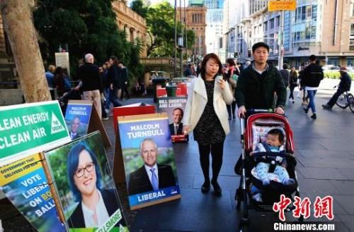 本届大选华裔选民热情高涨。图为一个亚裔之家正路过一家投票站。 赖海隆 摄