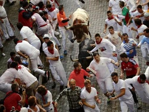 """在节日的几天里,每天都有6头凶悍的公牛追逐着人群,沿着""""奔牛之路""""穿城而过,直奔斗牛场,场面极其惊心动魄。(图片来源:美联社)"""
