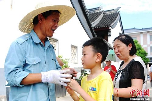 资料图:苏州一群小学生走上街头,将一杯杯调制好的冰镇酸梅汤端给在露天高温环境下工作的劳动者们。发 吴瞳 摄