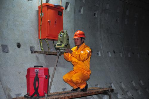 王斌在隧道内进行测量工作。来源:上海建工机施集团供图。