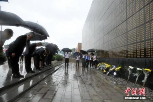 震后40年,海外侨胞唐山访亲,雨中向大地震纪念墙献花。(记者 翟羽佳 摄)