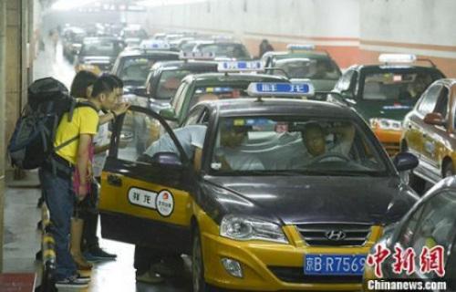 资料图:市民在北京西客站出租车候车点准备乘车。发 侯宇 摄
