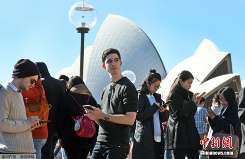 本地时刻7月15日,数十名大众在悉尼歌剧场前玩手机游戏《口袋魔鬼GO》。