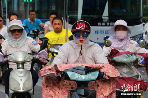 """7月26日,杭州市民""""全副武装""""出行。当日,浙江省气象台发布高温橙色预警,杭州最高气温为39.4℃。自7月20日以来该省高温已持续7天,有40个县市最高气温超过38℃。 记者 何蒋勇 摄"""
