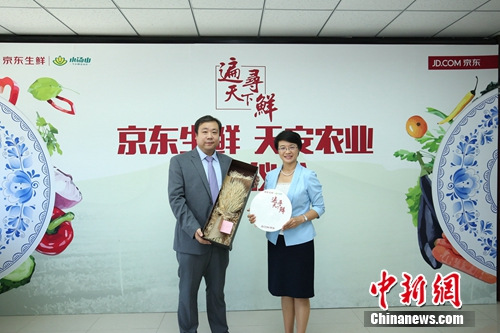 签约现场,京东生鲜与天安农业互赠礼品。