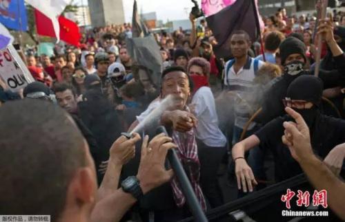 当地时间8月2日,巴西尼泰罗伊,里约奥运会火炬传递行进途中,示威者闹场与警方激烈冲突,抗议里约奥运会花费。图为警察向示威者喷胡椒喷雾。