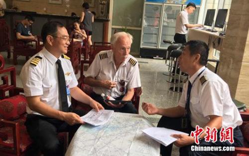 8月7日早上八点半,张博(左)和机械师奥维尔?雅格尔(中)、导航员康建生(右)围坐在一起,讨论环飞事宜。
