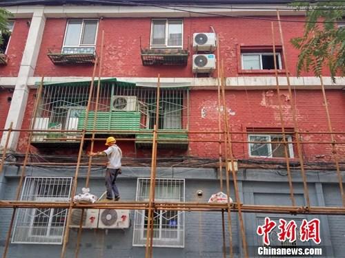 图为在北京某小区工作的农民工。吕春荣 摄