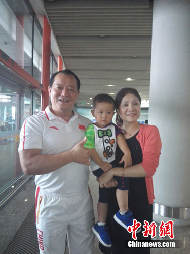 中国女子举重队主教练王国新和前来接机的家人。 尚虹波 摄
