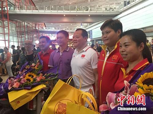 18日中午抵达北京首都国际机场的部分中国举重运动员、教练在机场大厅合影。 张�B 摄